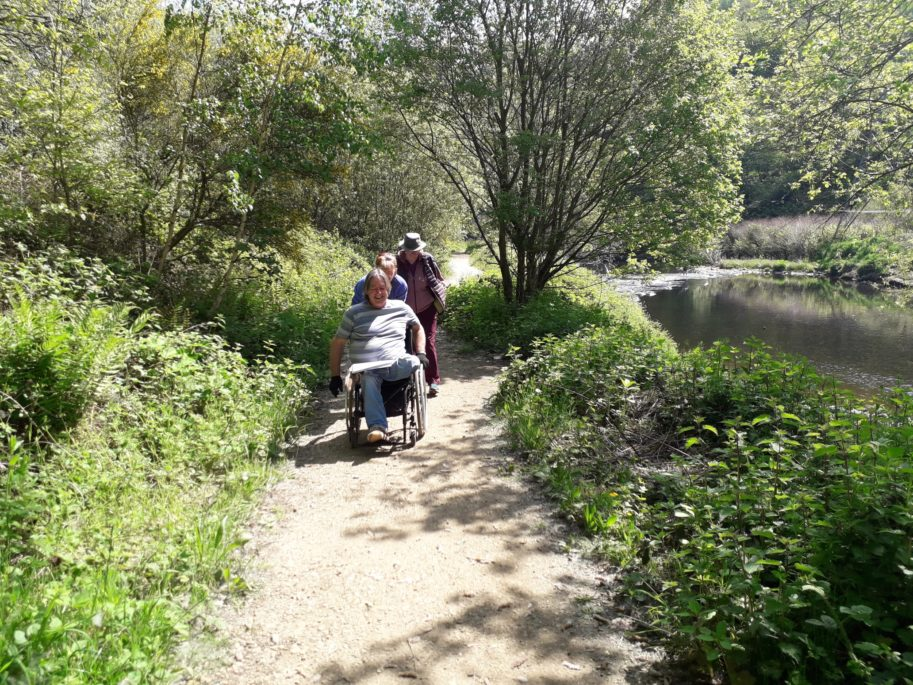 Chris Kamis wheeling his wheelchair by the side of a river. He's smiling and has two other people with him.