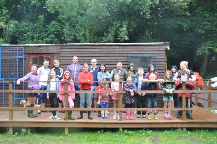 Sunnyvale Outdoor Centre Image of all age groups of volunteers outside a wooden cabin
